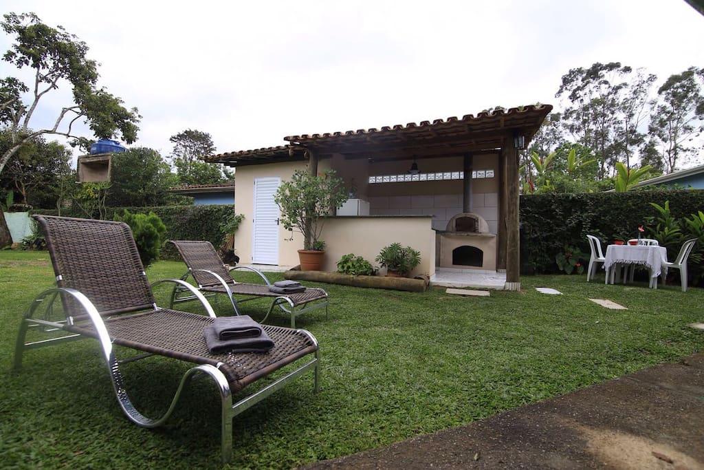 Área externa com fogão, geladeira, churrasqueira e forno de pizza! As espreguiçadeiras estão disponíveis para que desfrutem do sol!