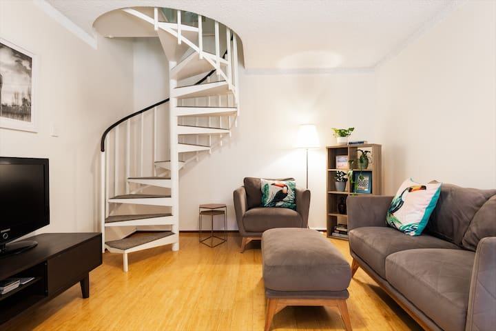Lounge room, stairs to bedrooms and bathroom