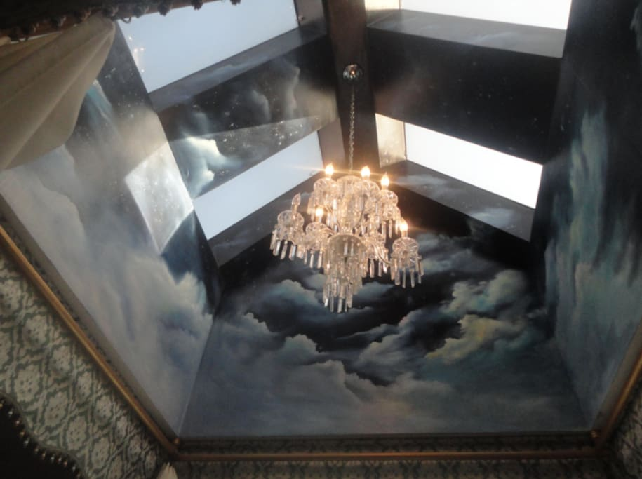 Hand painted mural and skylight with crystal chandelier above the bed