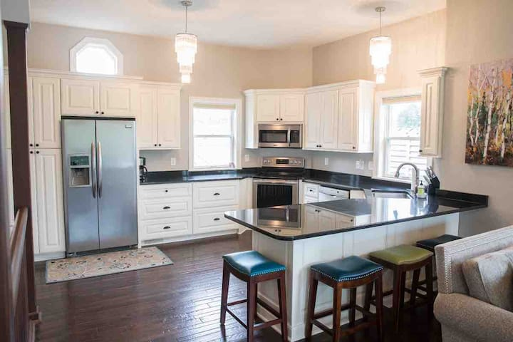 Spacious and airy kitchen is open to the Living Room & Dining area. 4 counter-height stools. Stocked with all types of kitchen essentials for meal prep: pots & pans, measuring cups, serving utensils, crockpots & toaster, dishware & glasses