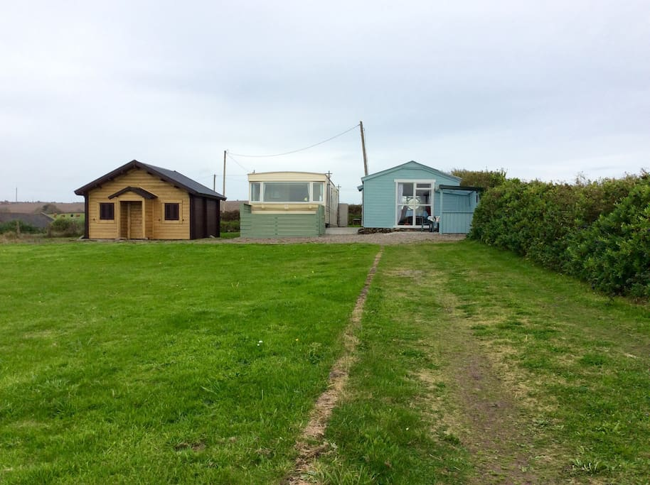 The site showing the blue bach, the mobile home and the brown cabin