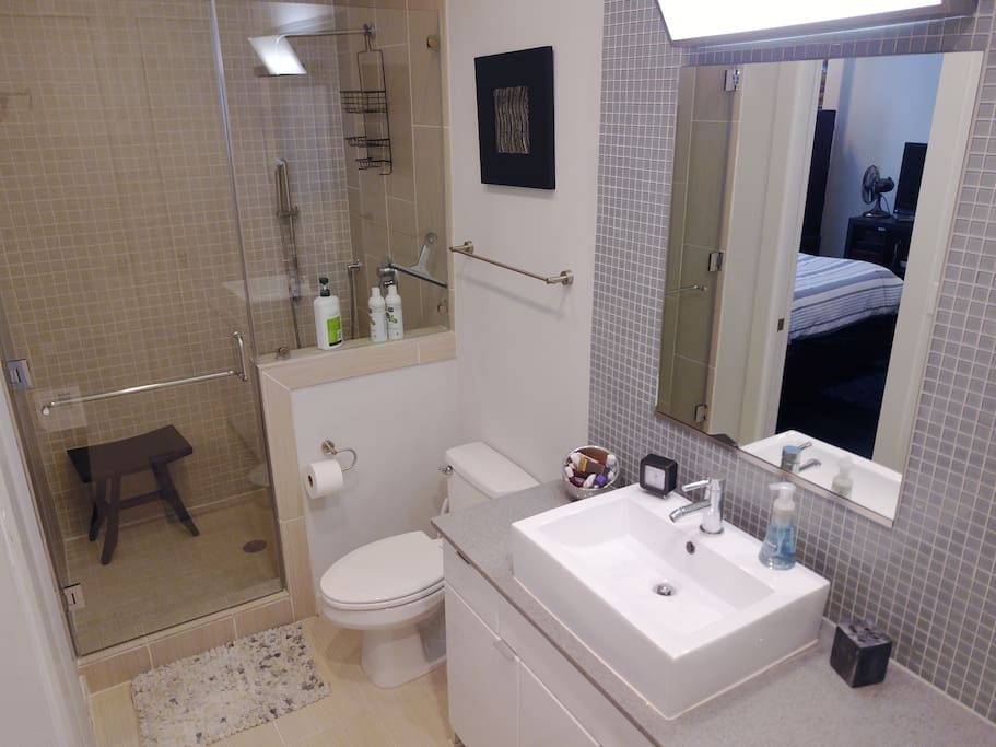Bathroom has a glass shower with rainfall head and wand. Bathroom is accessible from the bedroom or the living area. Washer and dryer are enclosed in the bathroom as well.