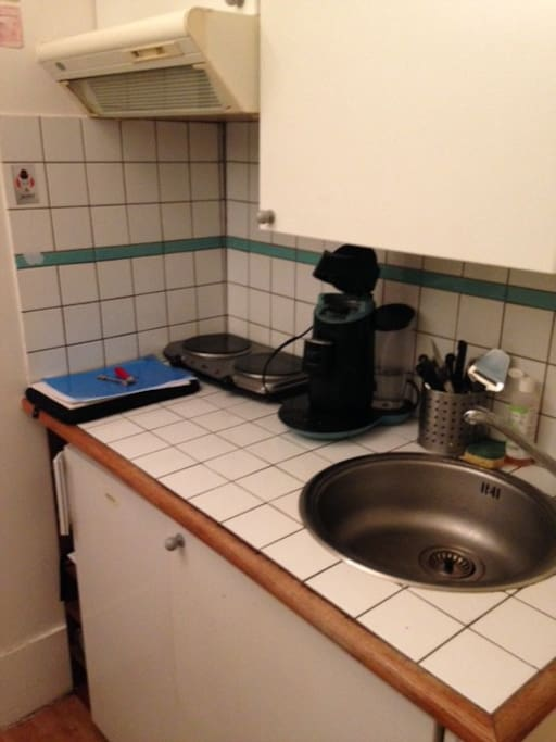 kitchenette avec un frigo, 2 plaques de caisson, machine à café, vaisselle.