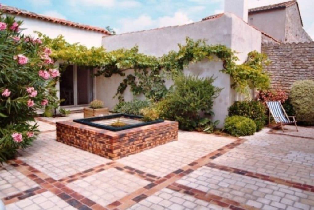 La cour commune aux 3 maisons, son bassin avec poissons et nénuphars, sa vigne et son laurier rose
