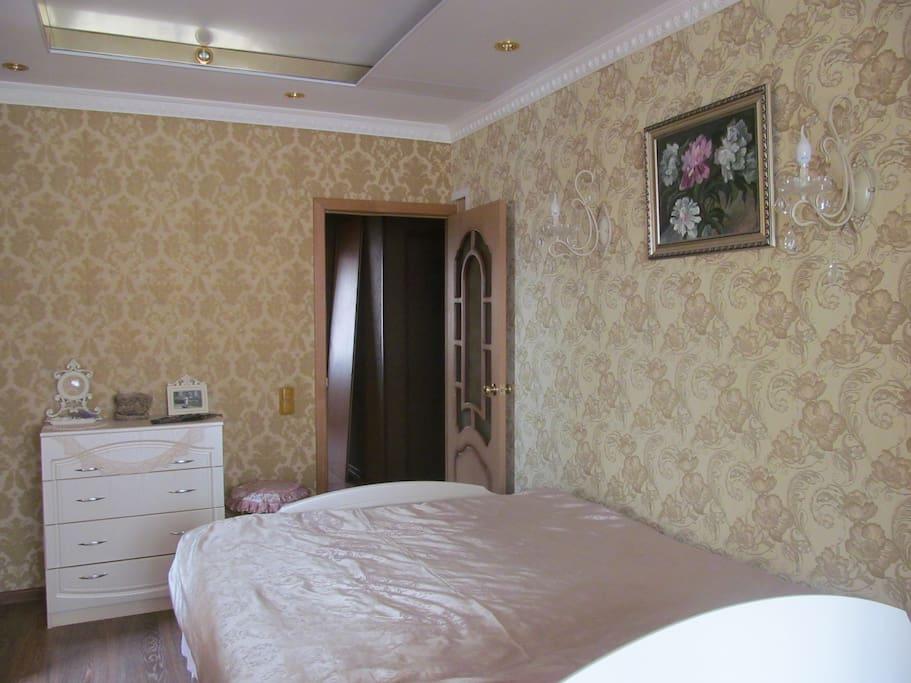Элегантная светлая спальная с одной двуспальной кроватью,комодом и тумбочкой