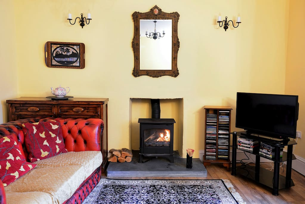 guests lounge with  cosywoodburning stove and tv