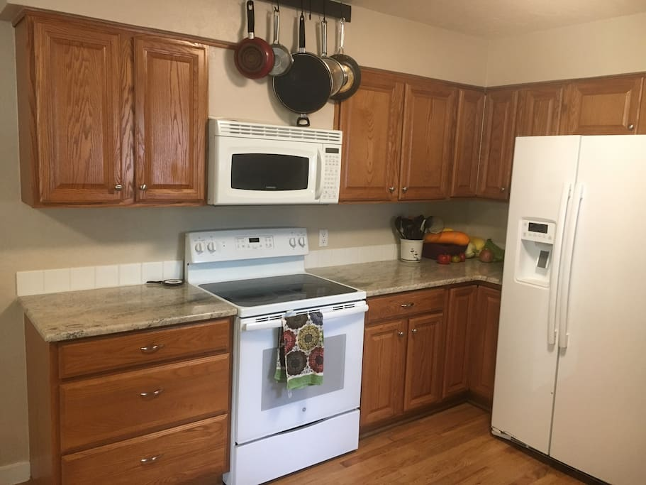 GE oven, microwave hood fan, and side by side refrigerator