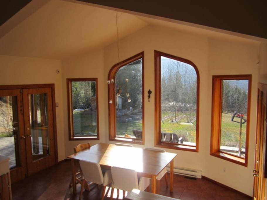 View from dining room out to gardens full of home-grown food for you to eat ! French doors with screens open onto patio.