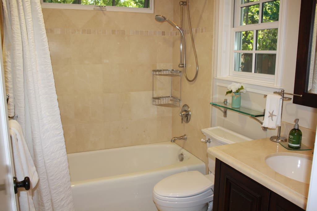 Sparkling full bath with marble and travertine