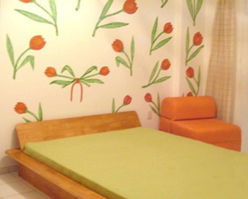 Suíte com cama de casal e um sofa-cama de solteiro.