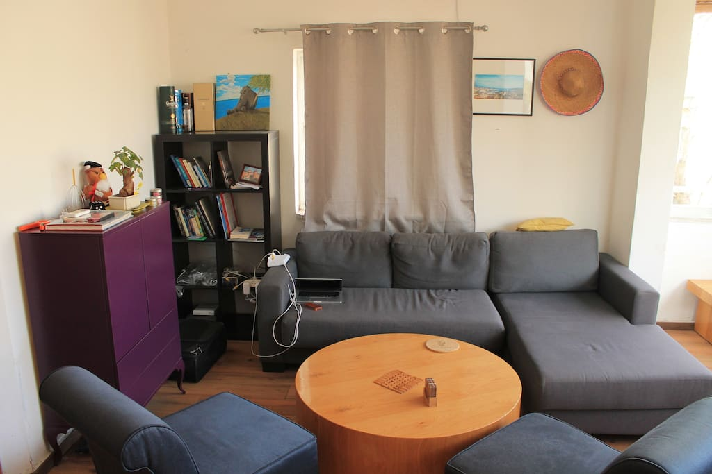 Living-room: big comfortable sofa, wooden table, two armchairs.
