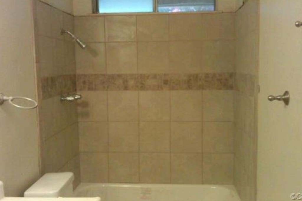 This is the bathroom adjacent to the room being rented. It features an expansive counter top, an array of drawers, and a tiled shower with a brand new, strong shower head.