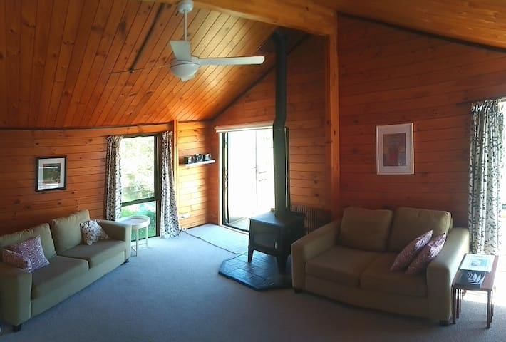 Cosy lounge with wood burner and French doors leading out to the deck