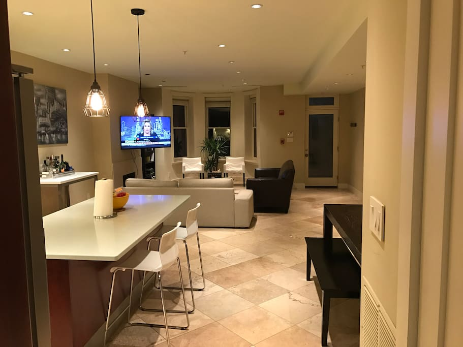Living room/dining room/kitchen. TV swivels to face any direction in the room.