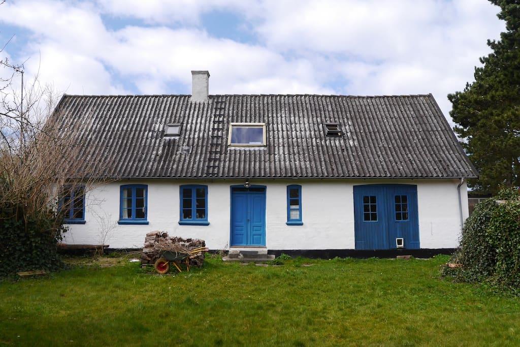 Huset set fra haven med indgangsdør.
