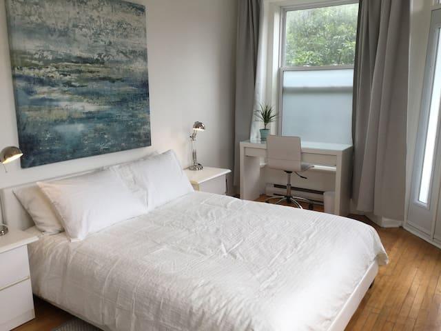 Chambre blanche ensoleillée avec balcon