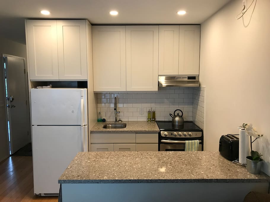 Modern and convenient - full sized fridge and cooktop with stone benchtops. Our kitchen is set up for chefs. Coffee, tea, salt, pepper are provided so you can self-cater your entire stay.