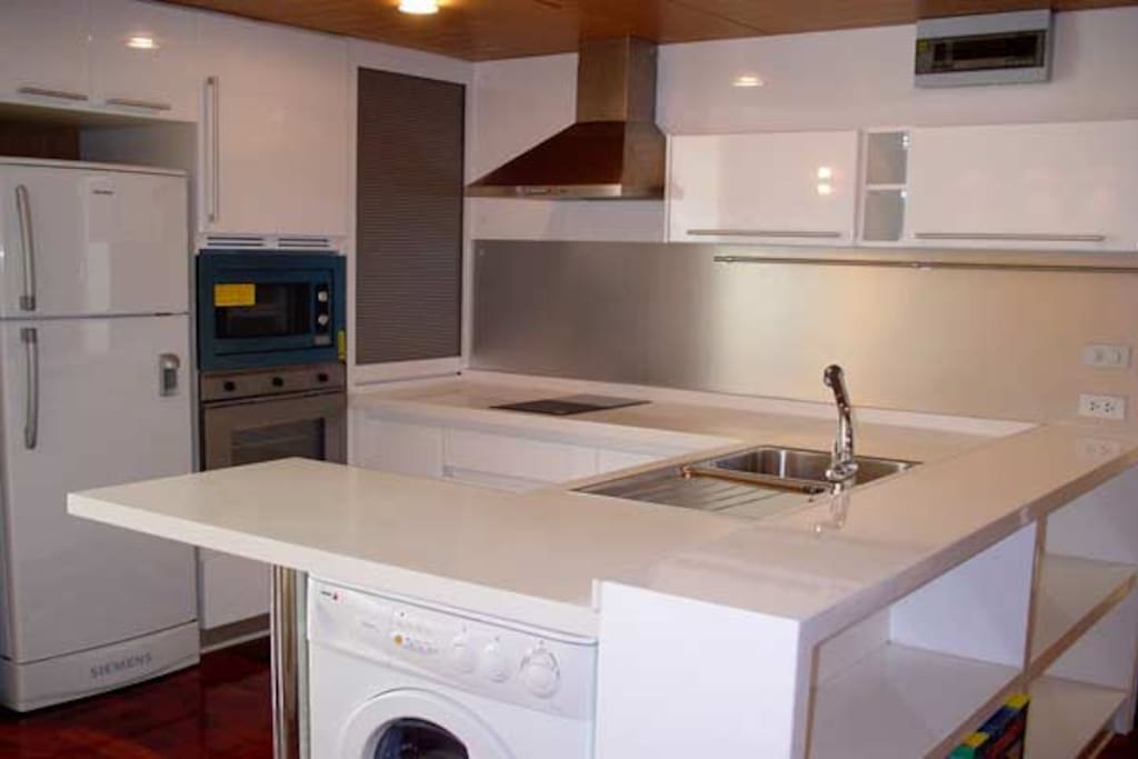 kitchen with fridge oven, microwave and stove. A washing machine.