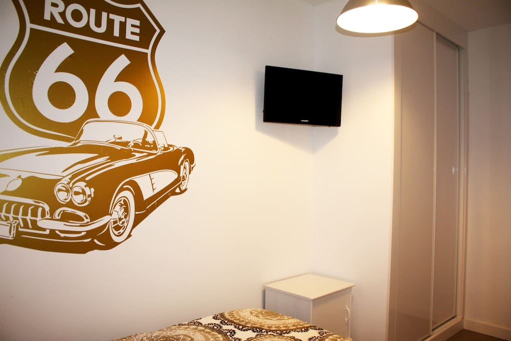 Habitación decorada con un original vinilo en la pared y tonos blanco y tierra.