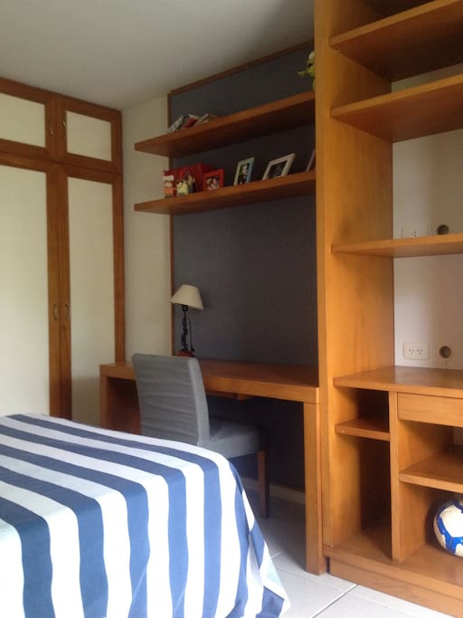 Mesa de estudos, cadeira TOK & STOK e armários no quarto.