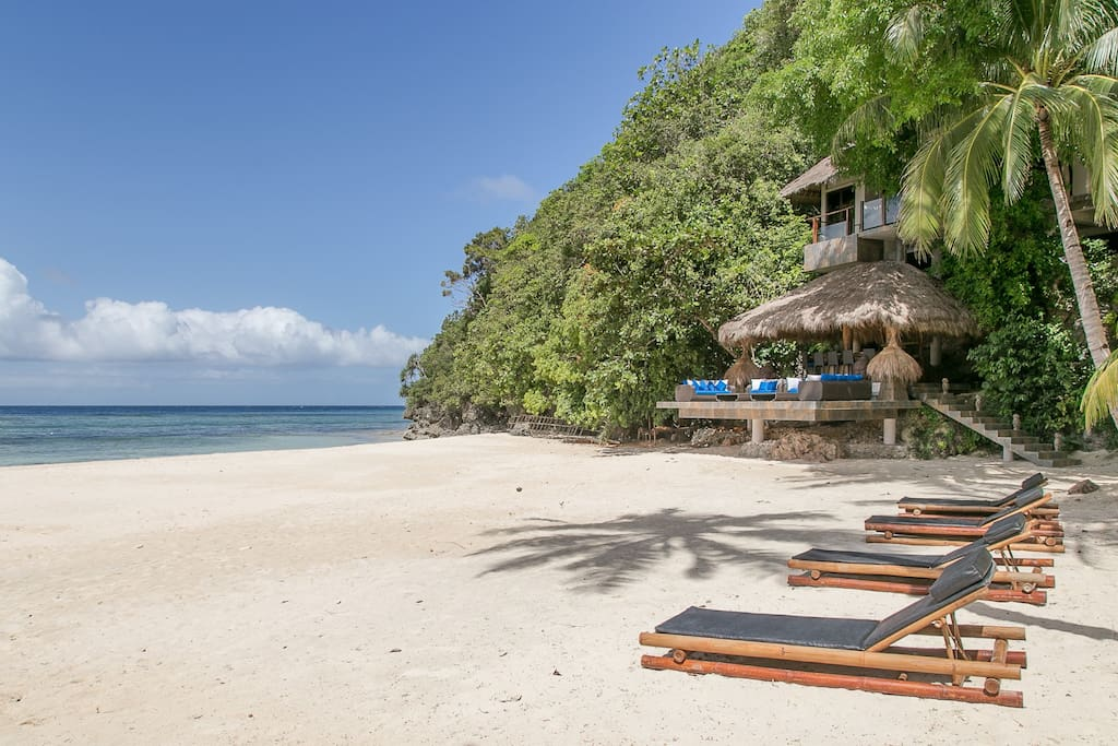 Exclusive beach front with beach loungers and a mini bar facing the sea.
