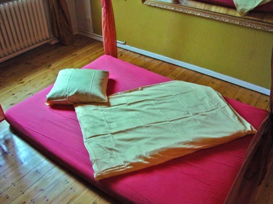 Futonbett, 140 x 200 cm unter einem Betthimmel, heimelig und wohlig.
