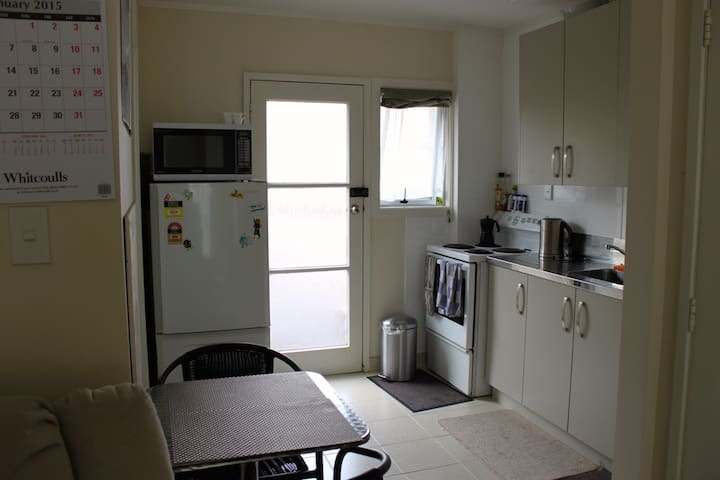 Looking into the kitchen at small table, fridge, front door.