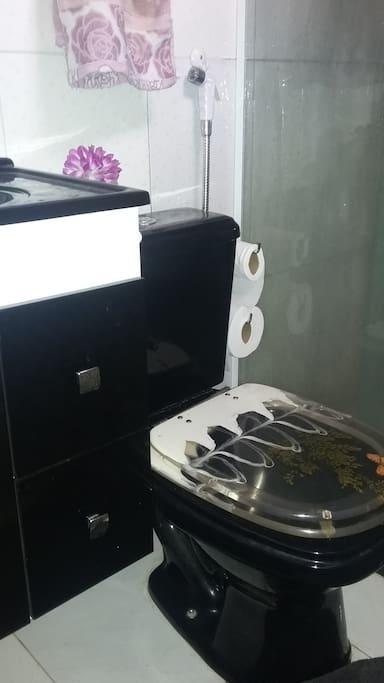 Banheiro com armário e suporte higiênico