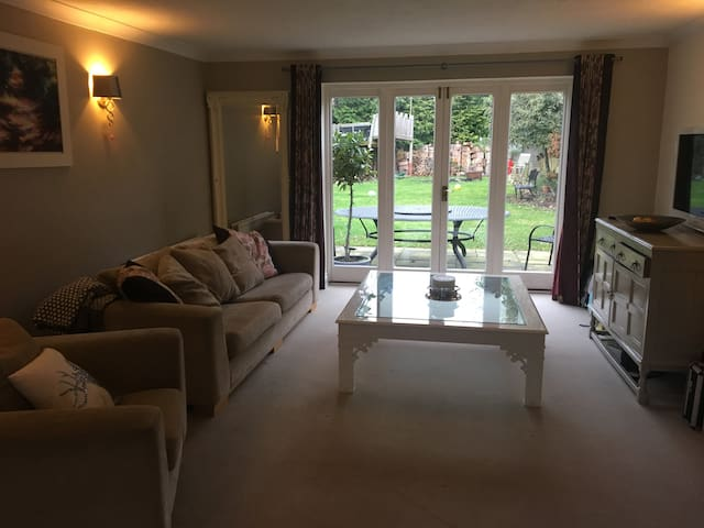 Large lounge with gas fire place, plenty of space & light, access to the garden where there is a large black oval table thats seats 10-12.