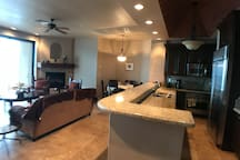 Lovely kitchen with granite countertops open to the living room area and a wall of glass to the sea.  Wall of glass opens totally for those times that you want to let the ocean sounds and sights in.