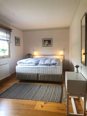 Sovrum 1 (nedre plan) med dubbelsäng och garderob och byrå