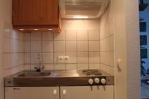 kleinen Küchenzeile mit 2 Kochplatten und Spüle. Kühlschrank mit Eisfach