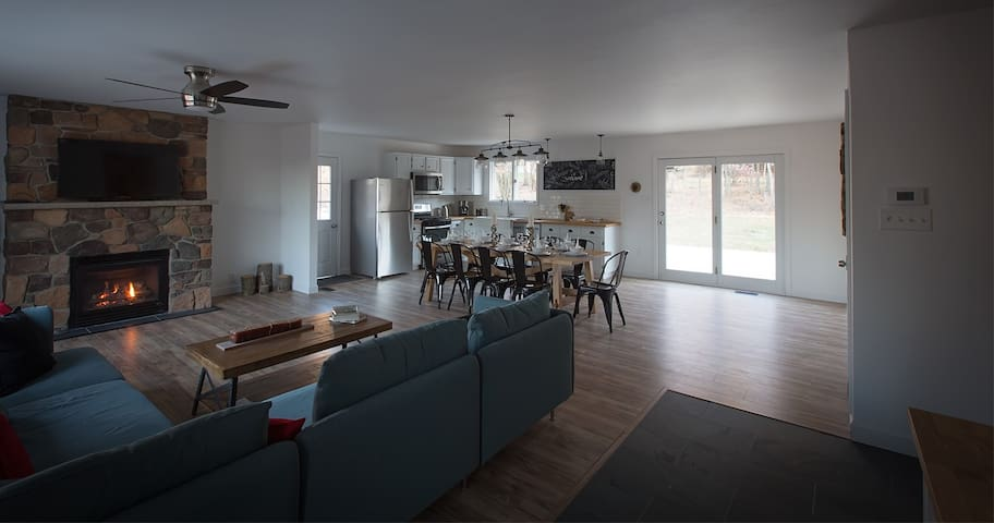 Open kitchen/dining/living area with doors leading to back deck for open indoor/outdoor living