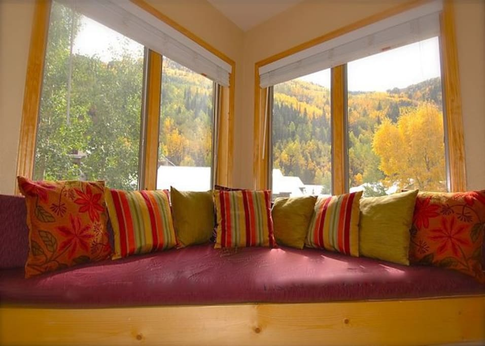 The condo has a bay window overlooking the garden & river, with the mountains surrounding town.