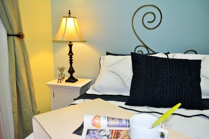 Cozy bedroom with comfy queen bed designed by one of our city's best metal sculptors.  TV positioned for great viewing  (not pictured).