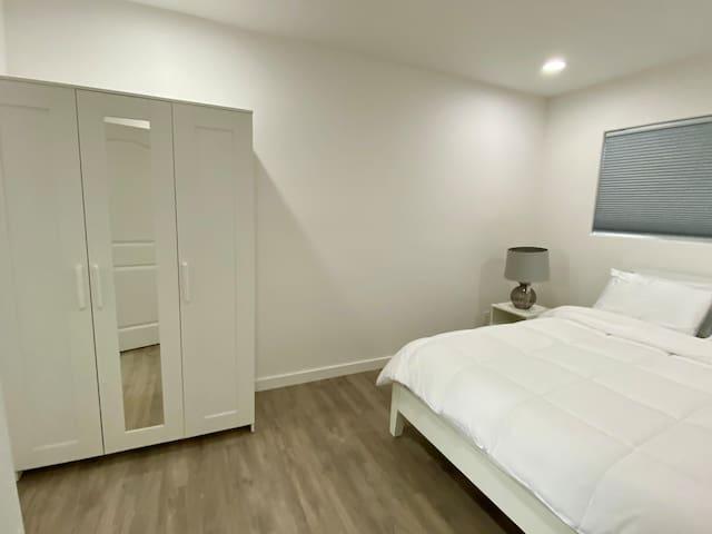 Queen size bed, bedroom #3, dresser with mirror.