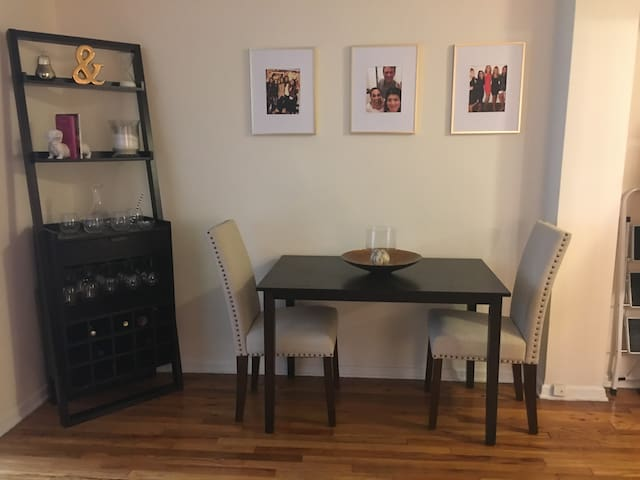 Wine bar with wine glasses and accessories. Table and chairs to sit and eat at or do work.