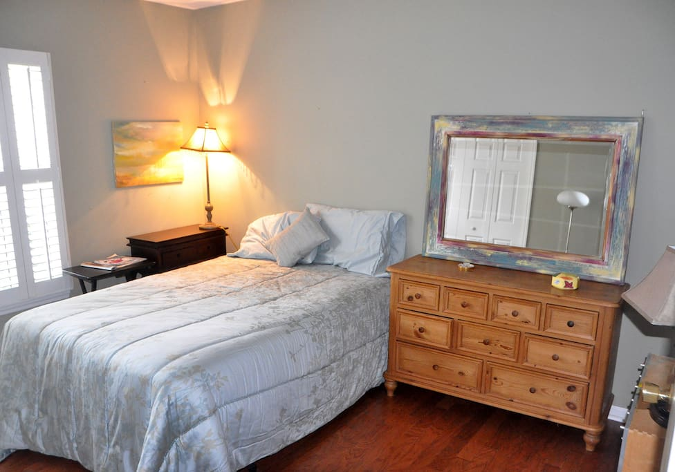 Double bed, closet and drawer space with plantation shutters