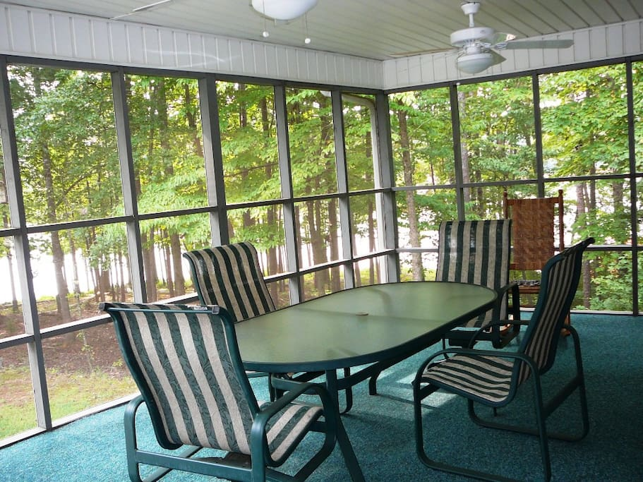 Spacious screen porch overlooking the lake, with two tables and chairs.