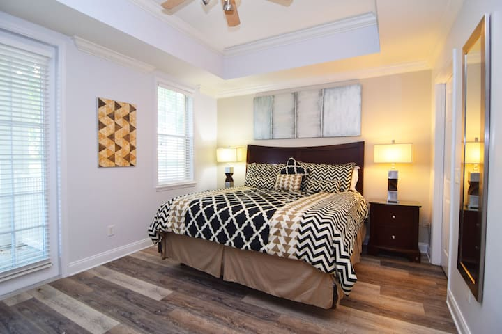 Stylish and spacious master bedroom with king bed, flat screen TV, doors to the balcony, en suite bathroom, walk-in wardrobe.