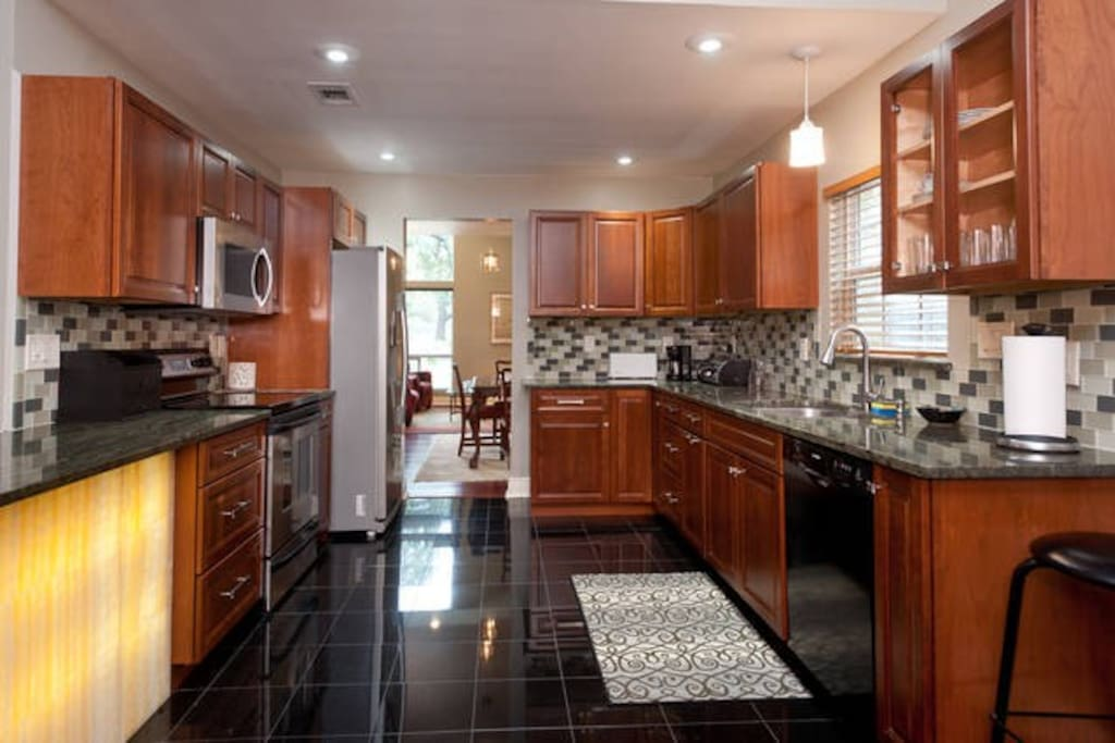 Kitchen:  new cabinets, glass tile backsplash, high-end appliances, backlit onyx feature under counter peninsula