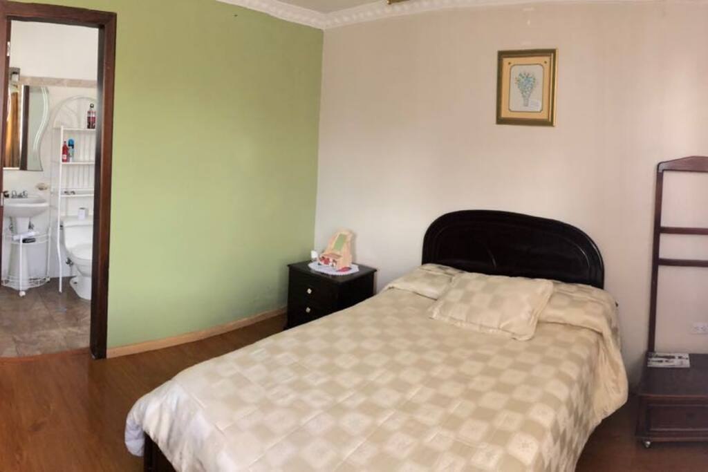 Amplio dormitorio con cama de dos plazas, baño completo privado,  TV, Wifi y mesa de trabajo.