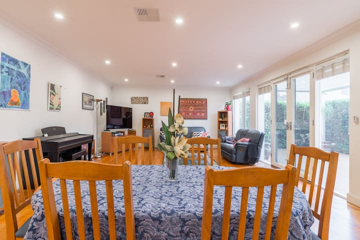 Living area with extendable dining table with 6 chairs, large screen TV and access to the outdoor patio area.