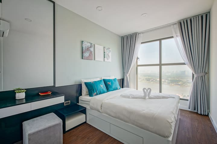 The first bedroom for 2 people. A cozy king size bed with bedding set, towels air-conditioner, closet with hangers inside, working table mixed with the make-up table. You can see the wonderful river and city view from this bedroom.