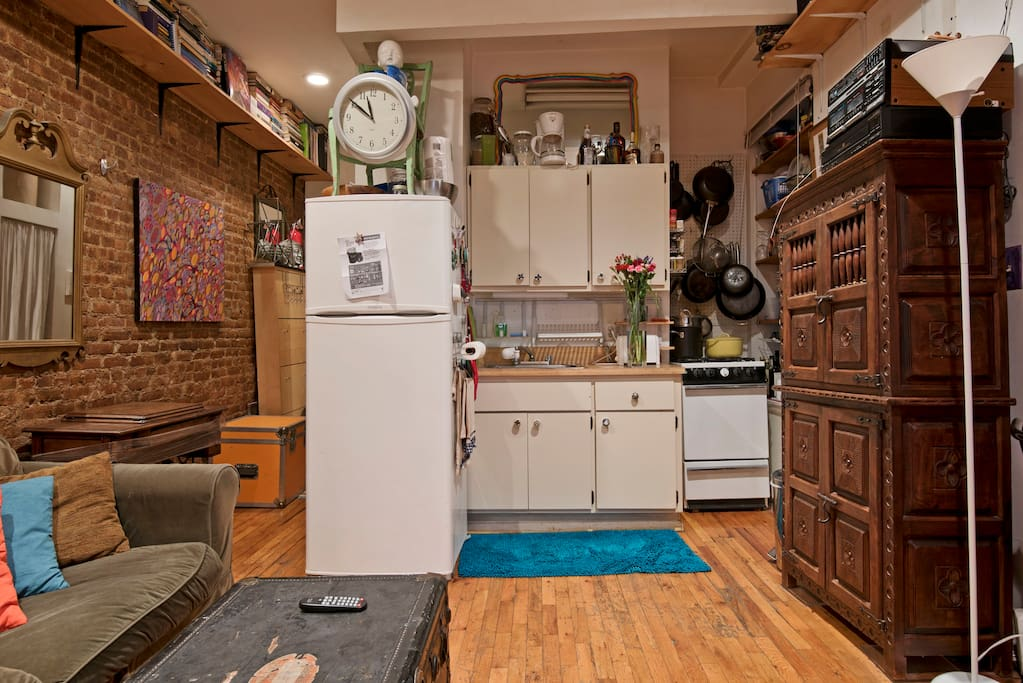 Another view of den/kitchenette. Notice hardwood, antiques, brick walls and very high ceiling and awesome lighting.
