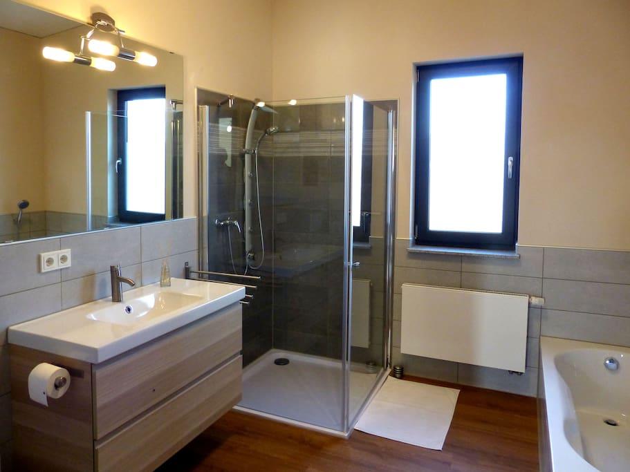 Badezimmer mit Dusche und Badewanne, Föhn, Handtücher