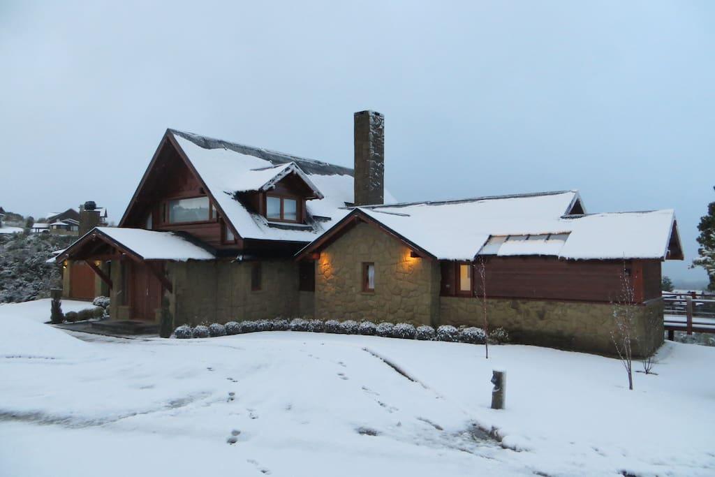 Vista del frente de la casa, luego de una nevada, al atardecer