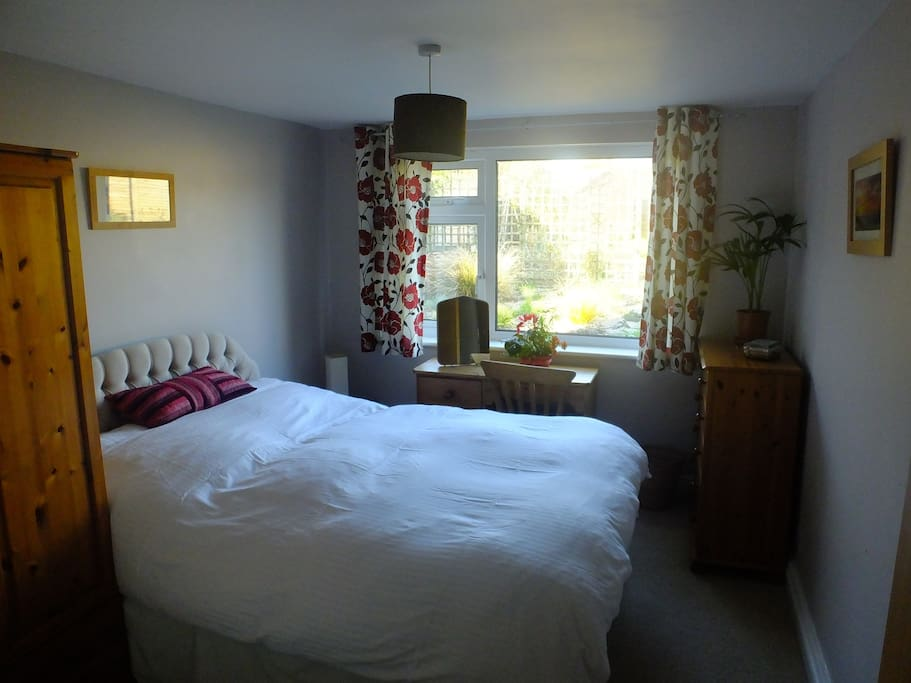 This is a double room with a comfortable bed and a view of the garden