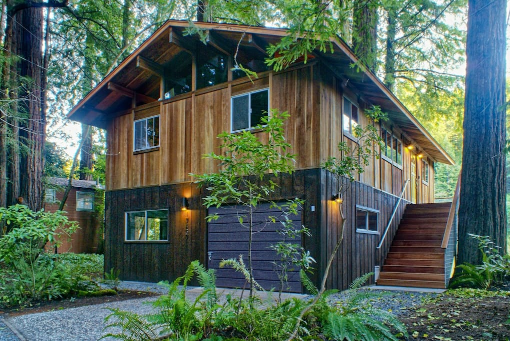 The house is nestled in the forest with garage parking for 2 vehicles, and driveway parking for 1 vehicle.