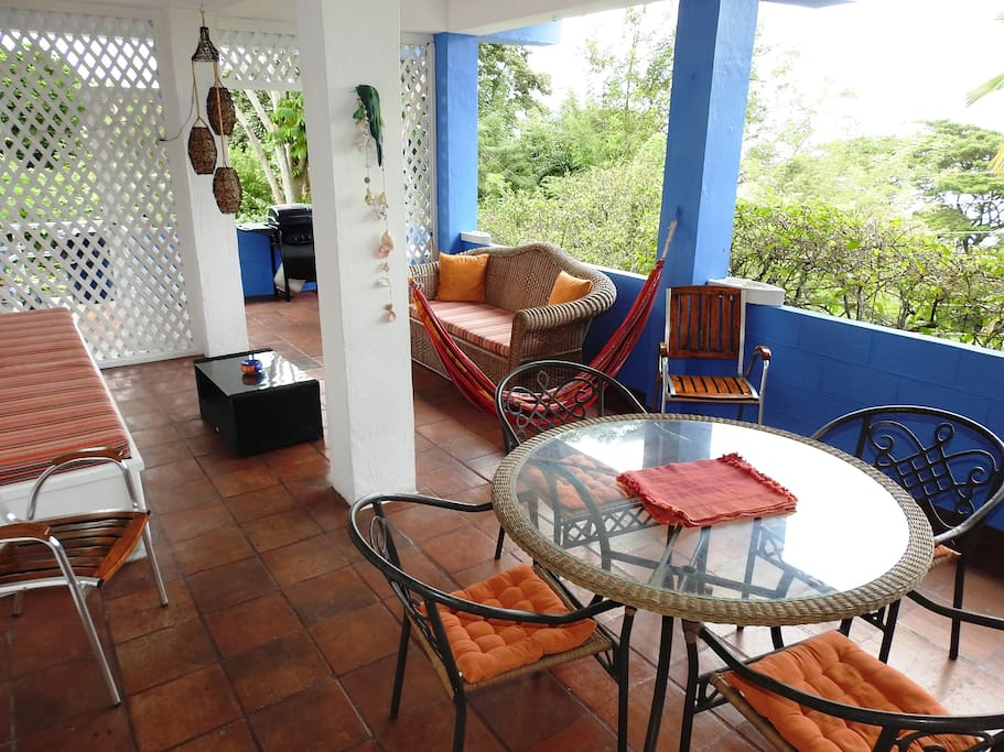 The apartment has a large balcony overlooking the pool and lush garden
